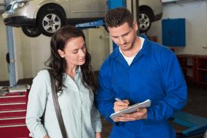 mechanic explains car service quote to woman