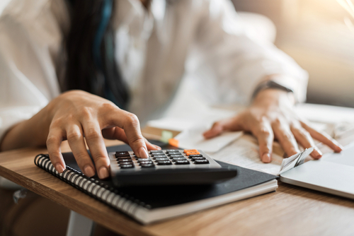 woman with calculator budgeting to lower car insurance premiums