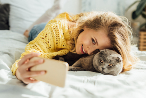woman in yellow taking selfie with cats for Instagram