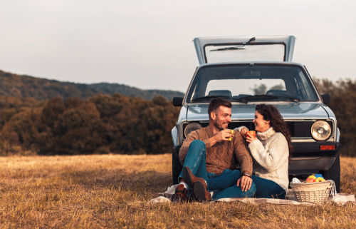 couple having picnic in front of blue old high mileage car