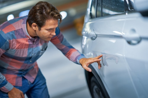 A man inspects the damage to his car and wonders about car scratch repair options.