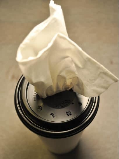 A washed and dried takeaway coffee cup and lid make a great tissue dispenser for your car