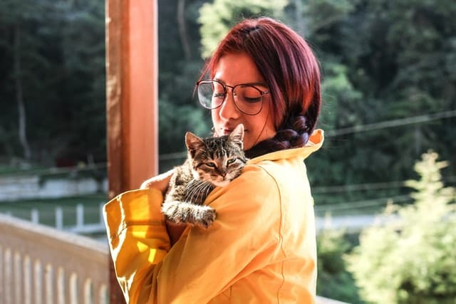 woman in yellow jacket cuddling foster cat on shoulder