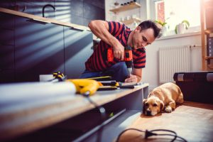 man with pet labrador dog doing construction work with sander