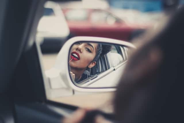 woman doing lipstick makeup in side mirror while driving